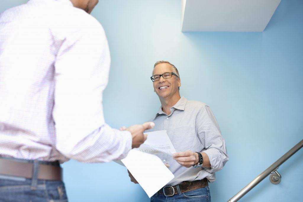 Businessmen talking in office stairwell